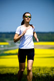 Jogging woman. A woman jogging in front of cross country royalty free stock photos