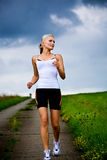 Jogging woman. A woman jogging in front of cross country stock images