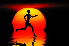 Jogging. Woman jogging against a sunset ocean Royalty Free Stock Photography