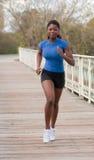 Jogging woman on bridge. Beautiful african woman jogging on bridge with smile stock photo