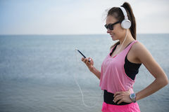 Jogging by woman. Favorite music played from her mobilephone Stock Photos