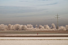 Jogging woman in frosted fields. Frosted landscape in winter with a woman running through the fields in the German countryside. Electrical transmission tower in Royalty Free Stock Photos