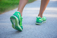 Jogging woman in green running shoes. Close up of jogging woman in green running shoes royalty free stock images