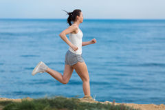 Jogging. Woman in jeans shorts and white tank top runs along seashore royalty free stock image