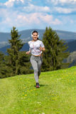 Jogging woman running in sunshine on beautiful summer day and listening a music in headphones. Royalty Free Stock Photo
