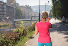Jogging woman setting phone before jogging Royalty Free Stock Photography
