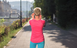 Jogging woman setting phone before jogging Royalty Free Stock Image