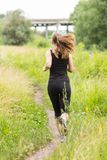 Jogging woman at summer midday. Stock Photos