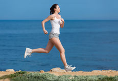 Jogging. Woman in white tank top and gray sports briefs runs along seashore stock photos