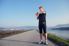 Before jogging. Young man sterted his watch Royalty Free Stock Images
