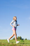 Jogging young sportive woman meadows sunny day. Sportive jogging young happy woman meadows blue summer sky Royalty Free Stock Photo