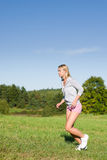 Jogging young sportive woman meadows sunny day. Sportive jogging young happy woman meadows blue summer sky Royalty Free Stock Photos