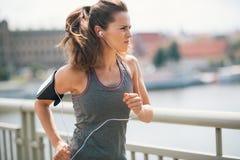 Joggingvrouw die op brug aan muziek luisteren Royalty-vrije Stock Afbeeldingen