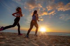 Jogginr för flickor för solnedgångstrand två färdig på sand royaltyfri bild