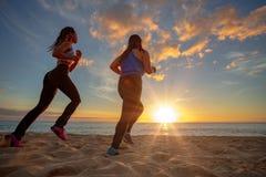Jogginr för flickor för solnedgångstrand två färdig på sand royaltyfri foto