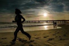 Joggs de la mujer en la playa Imagenes de archivo