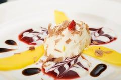 Joghurt-Kremeis mit Mangofruchtscheiben Stockfotografie