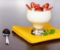 Joghurt mit Erdbeerescheiben auf einer gelben Serviette Lizenzfreies Stockbild