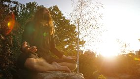 Jogi, das auf Sonnenuntergang meditiert stock footage