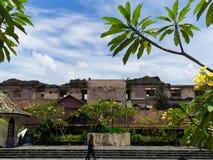 JOGJA,印度尼西亚- 2O17 8月12, :走在jogja的日惹一个恶劣的城市都市房子附近的未认出的人民 免版税库存照片