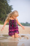 Jogo adorável da menina com a areia molhada na praia do oceano do por do sol Fotografia de Stock