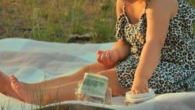 Jogo adorável da menina com dinheiro na cobertura no parque vídeos de arquivo