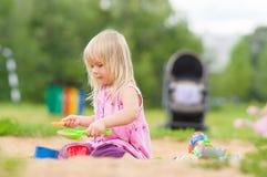 Jogo adorável da menina com os brinquedos na caixa de areia Fotos de Stock Royalty Free