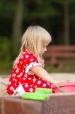 Jogo adorável da menina com os brinquedos na caixa de areia Fotografia de Stock Royalty Free