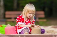 Jogo adorável da menina com os brinquedos na caixa de areia Imagens de Stock Royalty Free