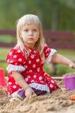 Jogo adorável da menina com os brinquedos na caixa de areia Fotos de Stock