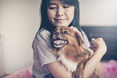 Jogo asiático alegre da jovem mulher e divertimento feliz com seu cão Foto de Stock Royalty Free