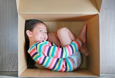 Jogo asiático pequeno feliz da menina da criança e encontro na caixa de cartão grande fotos de stock