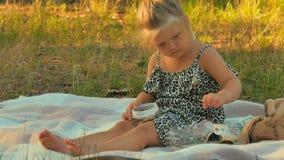Jogo bonito da menina com dinheiro na cobertura no parque do verão vídeos de arquivo