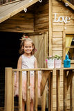 Jogo bonito da menina com lata molhando em uma casa na árvore Foto de Stock