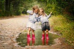 Jogo bonito de duas meninas na poça Foto de Stock