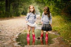 Jogo bonito de duas meninas na poça Fotos de Stock Royalty Free