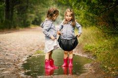 Jogo bonito de duas meninas na poça Imagens de Stock Royalty Free