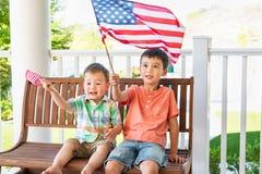 Jogo caucasiano chinês bonito dos irmãos da raça misturada com bandeiras americanas fotos de stock