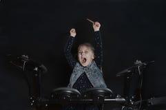 Jogo caucasiano pequeno do baterista da menina o jogo elettronic do cilindro Fotografia de Stock