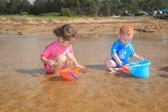 Jogo da água e da cubeta na praia Fotografia de Stock