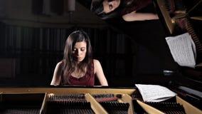 Jogo da m?sica do piano do m?sico do pianista Piano de cauda do instrumento musical com executor da mulher vídeos de arquivo