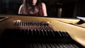 Jogo da m?sica do piano do m?sico do pianista Piano de cauda do instrumento musical com executor da mulher video estoque