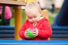 Jogo da menina com a esfera de borracha no campo de jogos Fotografia de Stock Royalty Free
