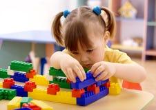 Jogo da menina com os tijolos do edifício no pré-escolar imagens de stock