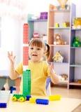 Jogo da menina com os tijolos do edifício no pré-escolar Fotografia de Stock