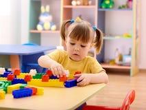 Jogo da menina com os tijolos do edifício no pré-escolar Fotos de Stock