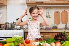 Jogo da menina da criança e divertimento ter com cerejas, frutas e legumes na cozinha home interior, conceito saudável do aliment imagens de stock royalty free