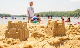 Jogo das crianças na praia com areia foto de stock