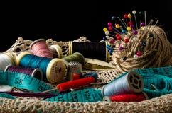 Jogo de costura com os carretéis da linha e das agulhas no fundo preto foto de stock