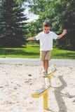 Jogo de criança no feixe de equilíbrio da estrutura do jogo do parque foto de stock